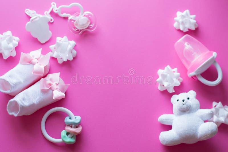 Acessórios e brinquedos do bebê no fundo cor-de-rosa Vista superior o plano da criança coloca com brinquedos brancos fotografia de stock royalty free