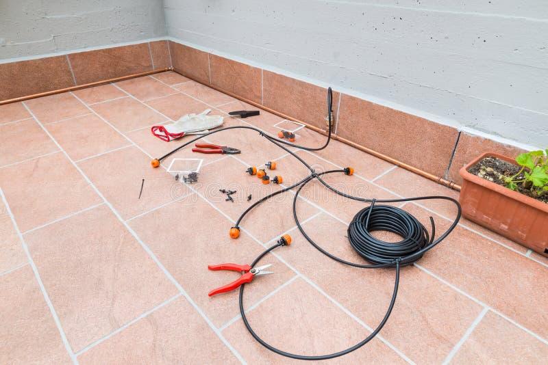 Acessórios e materiais para terminar um micro sistema de irrigação do gotejamento para plantas em pasta no terraço foto de stock