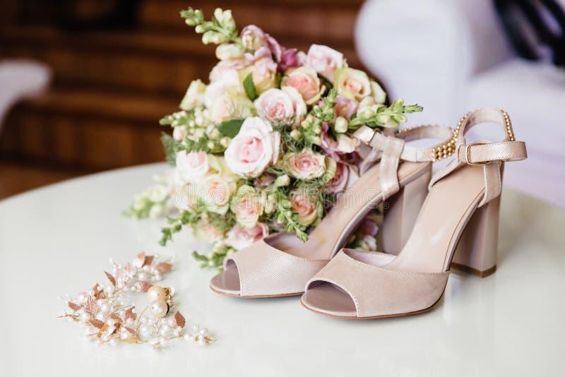 Acessórios e roupa da noiva, close-up Sandálias bege, ramalhete nupcial, decorações do cabelo do ` s da noiva, brincos imagens de stock royalty free
