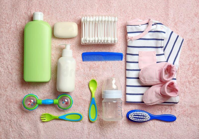 Acessórios e roupa do cuidado do bebê no fundo claro, fotografia de stock