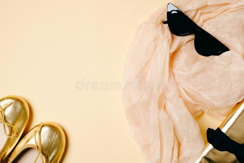 Acessórios fêmeas ajustados no fundo bege, local de trabalho da mulher Lenço, óculos de sol, deslizadores dourados do verão, saco imagens de stock