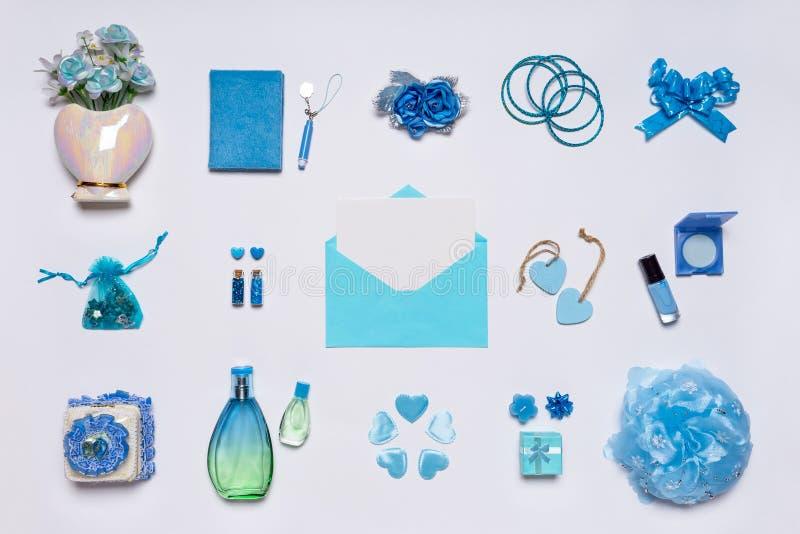 Acessórios femininos à moda, flores, cosméticos, joia, perfume em cores pastel azuis no fundo branco Envelope com placa imagem de stock
