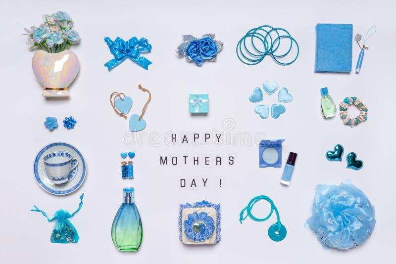 Acessórios femininos à moda, flores, cosméticos, joia, perfume em cores pastel azuis no fundo branco MÃES FELIZES do texto imagens de stock royalty free
