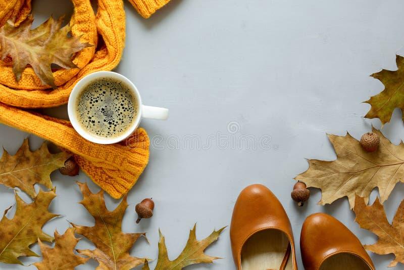Acessórios femininos do outono Lenço e sapatas, xícara de café, folhas do carvalho e bolotas no fundo de madeira cinzento Configu imagem de stock royalty free
