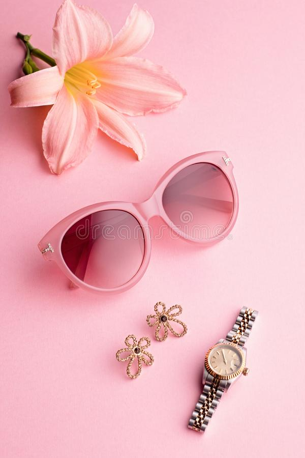 Acessórios glamoroso da mulher - relógio, óculos de sol, brincos e flor do lírio Composição feminino no fundo cor-de-rosa imagens de stock