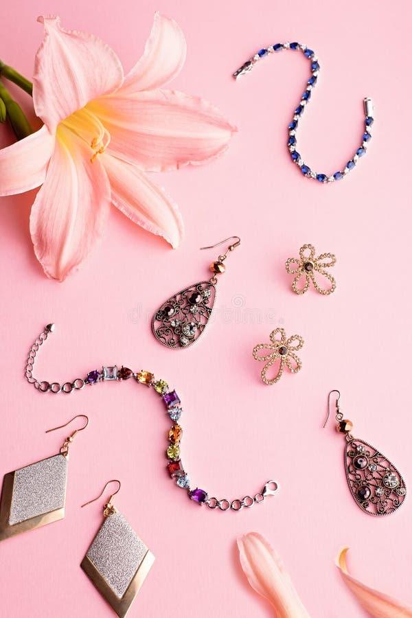 Acessórios glamoroso e joia da mulher Composição feminino no fundo cor-de-rosa com flor do lírio foto de stock