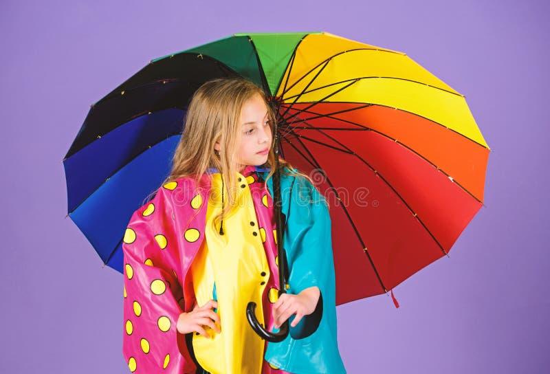 Acessórios impermeáveis para crianças Os acessórios impermeáveis fazem o dia chuvoso alegre e agradável Posse feliz da menina da  foto de stock