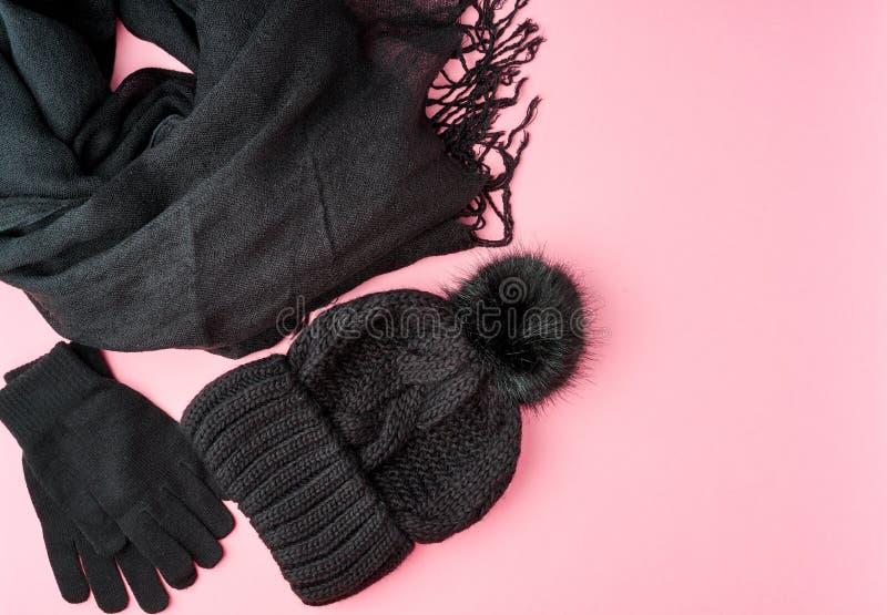 Acessórios mornos colocados lisos da mulher do inverno ou do outono - lenço feito malha preto, chapéu no fundo cor-de-rosa brilha fotografia de stock royalty free