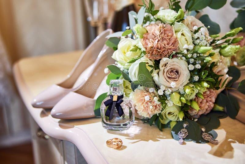 Acessórios nupciais tais como a mentira das sapatas, do ramalhete, do anel e do perfume em uma tabela imagens de stock