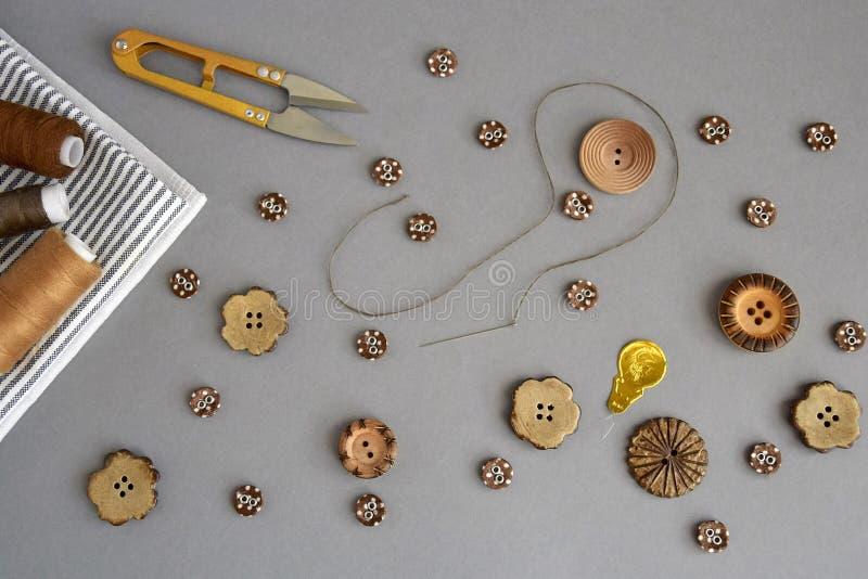 Acessórios para costurar e bordado: botões, tesouras, agulha com linha, grupo de carretel da linha, matéria têxtil, vista superio fotografia de stock