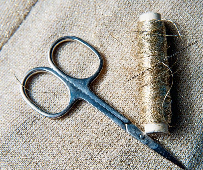 Acessórios para costurar na matéria têxtil dourada fotografia de stock