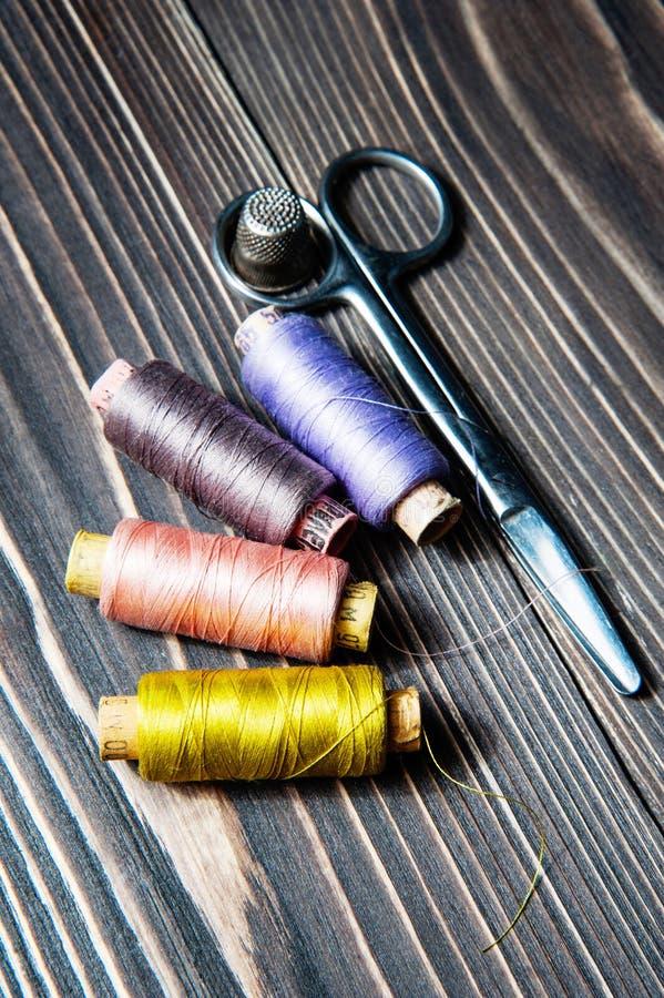 Acessórios para costurar na tabela de madeira escura fotografia de stock royalty free