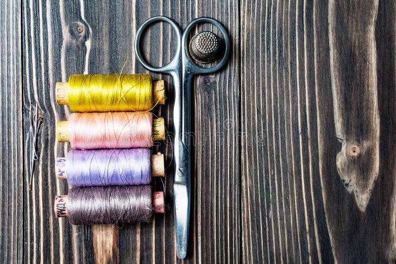 Acessórios para costurar na tabela de madeira escura foto de stock