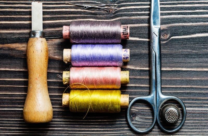 Acessórios para costurar na tabela de madeira escura imagem de stock royalty free