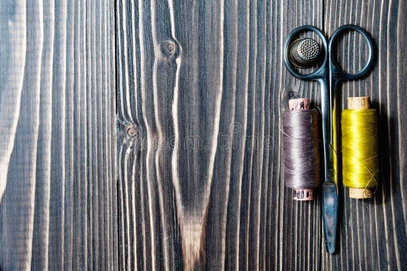 Acessórios para costurar na tabela de madeira escura foto de stock royalty free