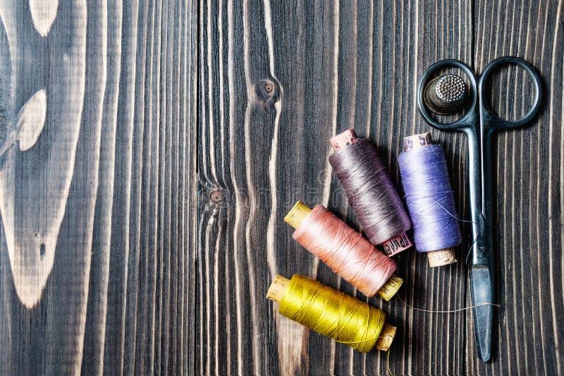 Acessórios para costurar na tabela de madeira escura imagem de stock