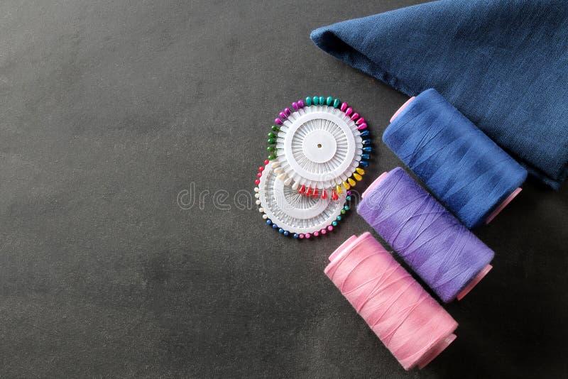 Acessórios para costurar uma bobina com linha, pinos e uma parte de pano em um fundo preto com um lugar para uma inscrição imagens de stock