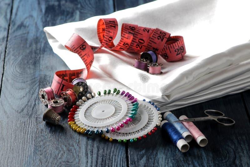 Acessórios para a linha costurar e de bordado, tela, tesouras, bobinas, pinos, centímetro em um fundo de madeira azul imagens de stock