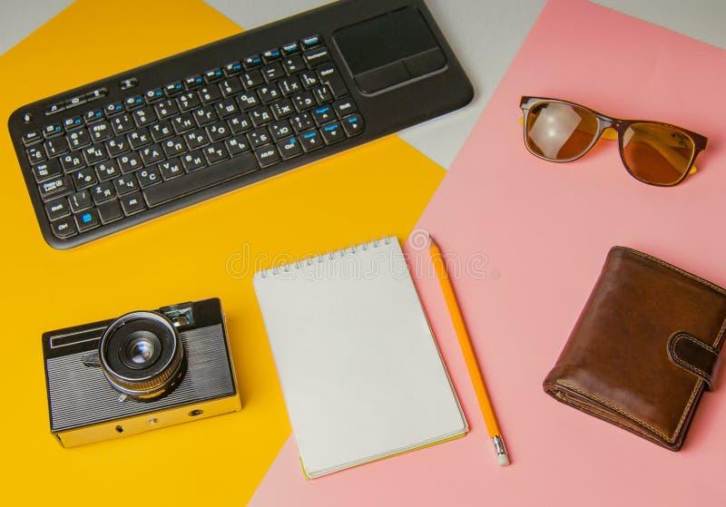 Acessórios para o trabalho com curso na praia: caderno, câmera do vintage, pena, óculos de sol, carteira em um amarelo e fundo co fotos de stock