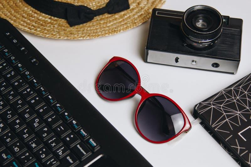 Acessórios para o trabalho com curso na praia: portátil, caderno, chapéu de palha, câmera do vintage, pena, óculos de sol em um f fotografia de stock