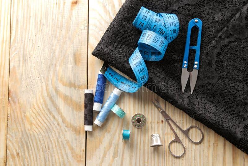 Acessórios para a tela costurar e de bordado, as tesouras, as bobinas e o centímetro no fundo da madeira natural imagens de stock