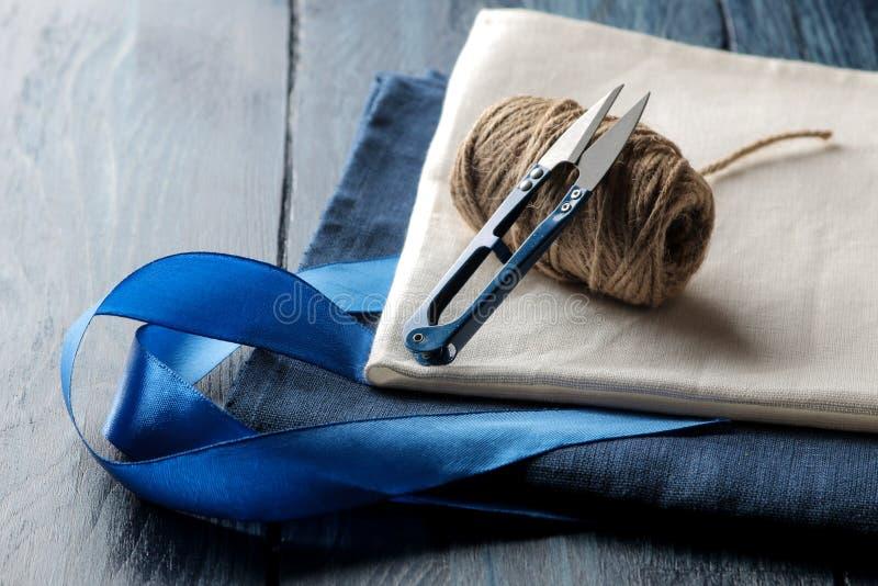 Acessórios para tesouras costurar e de linha e de tela do bordado em um fundo de madeira azul imagem de stock