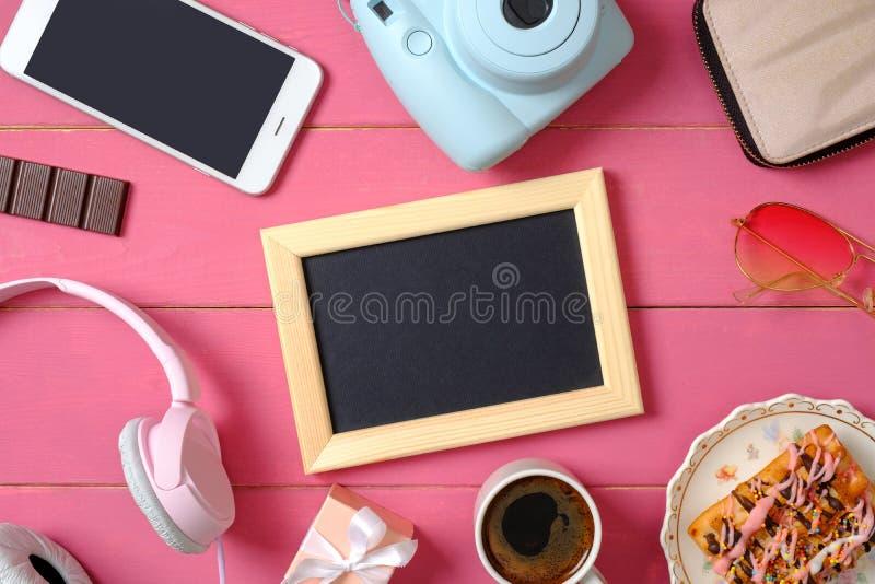 Acess?rios colocados lisos da menina no fundo de madeira cor-de-rosa Quadro da foto, câmera instantânea, smartphone, fones de ouv foto de stock