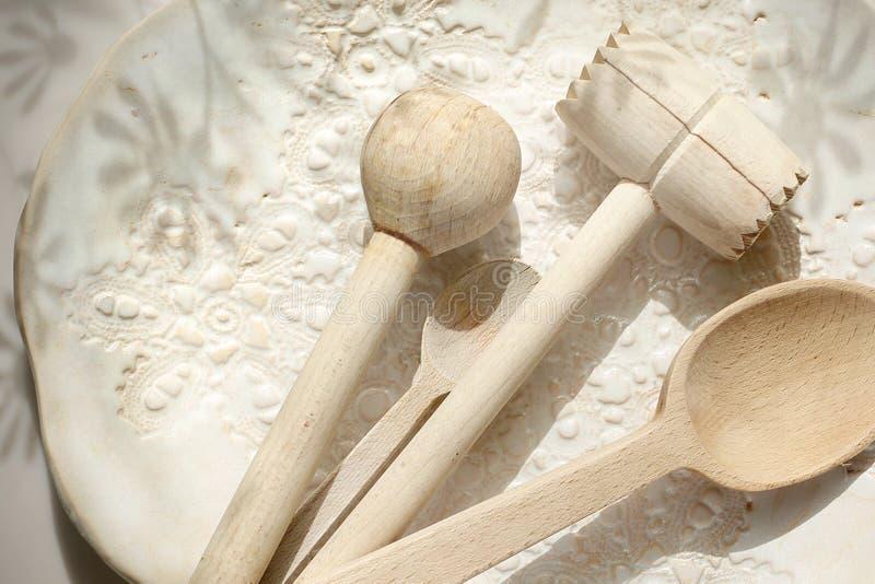 Acess?rios da cozinha Colher de madeira, vara e um pil?o da carne em uma placa decorada cer?mica imagens de stock