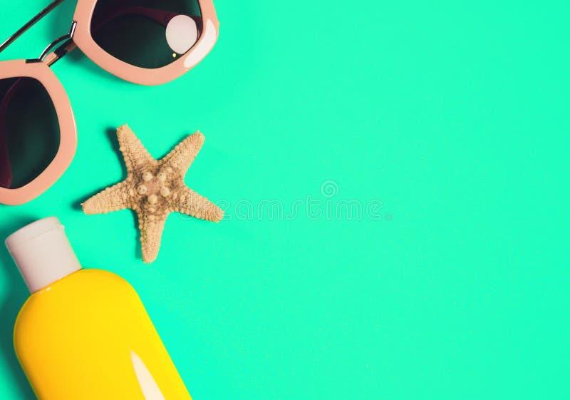 Acess?rios da praia em um fundo colorido verde-claro Estrela do mar secada, ?culos de sol cor-de-rosa e uma garrafa da lo??o da p fotos de stock