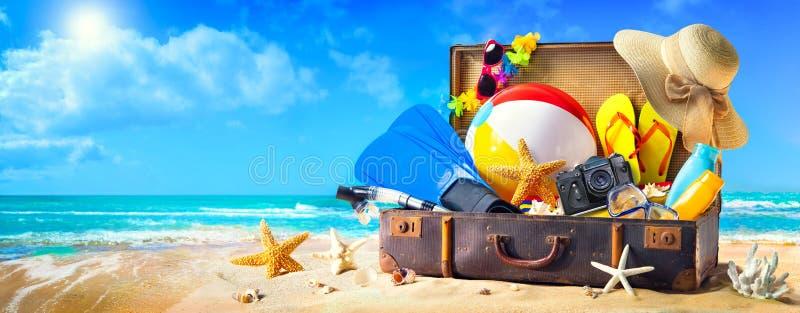Acess?rios da praia na mala de viagem na areia Conceito dos feriados da fam?lia imagens de stock royalty free