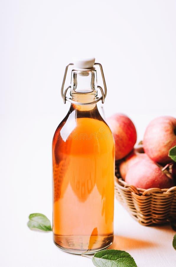 Aceto di Apple in una bottiglia sulla tavola di legno bianca con le mele in un canestro fotografia stock libera da diritti
