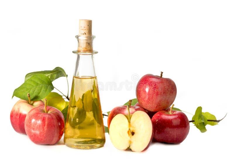 Aceto di sidro di Apple in una nave di vetro e nelle mele rosse fotografia stock libera da diritti