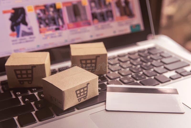 Achat en ligne - cartons de papier ou colis avec un logo de caddie et carte de crédit sur un clavier d'ordinateur portable Servic photographie stock libre de droits