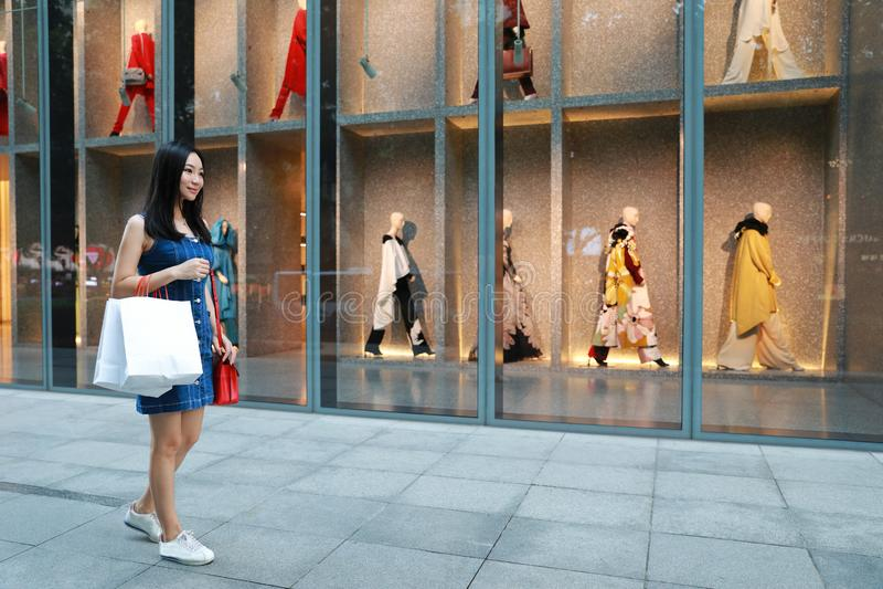 Achats à la mode orientaux orientaux chinois heureux de fille de femme de l'Asie jeunes dans le mail avec le fond de achat de fen image stock