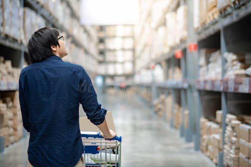 Achats asiatiques d'homme avec le chariot de chariot dans l'entrepôt images stock