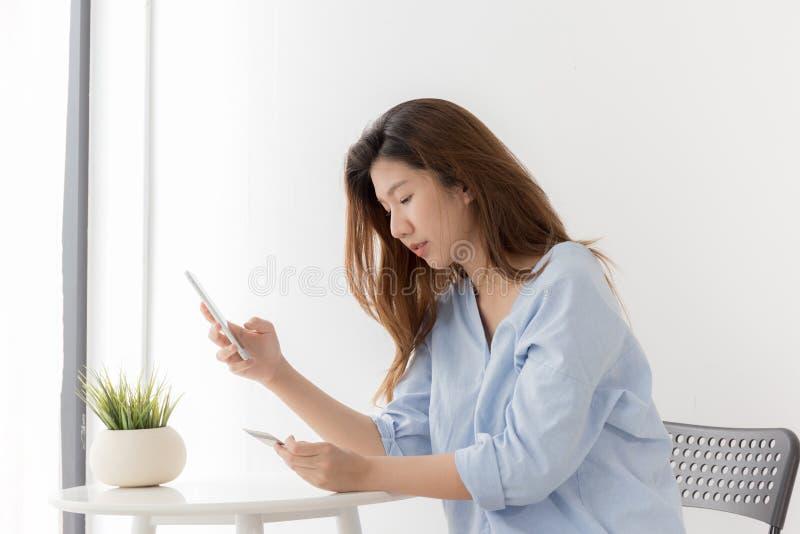 Achats asiatiques de femme avec le smartphone à la maison, wome de nouvelle génération photos libres de droits