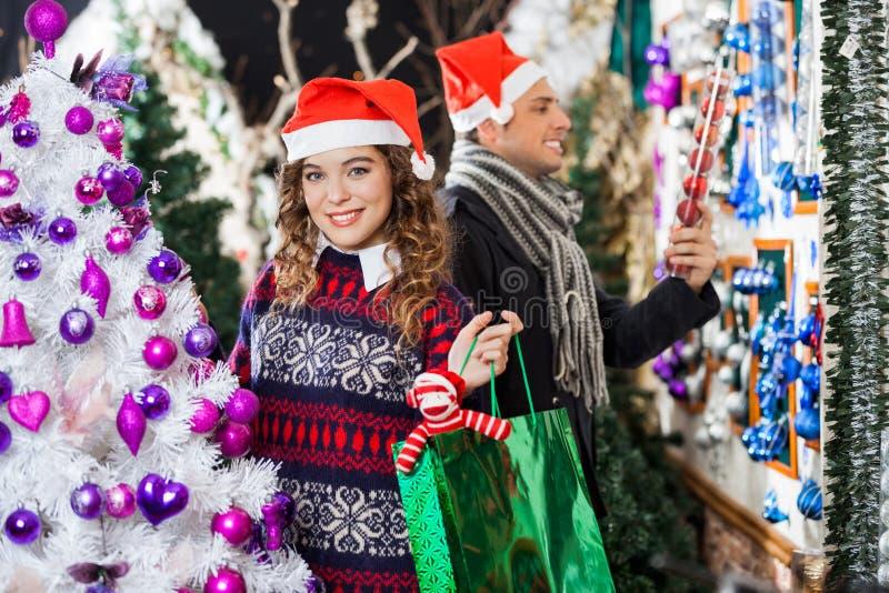 Achats d'homme et de femme dans le magasin de Noël images libres de droits