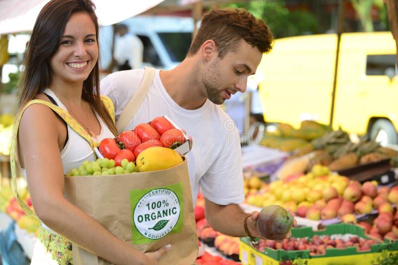 Achats de couples au marché en plein air ouvert. image libre de droits