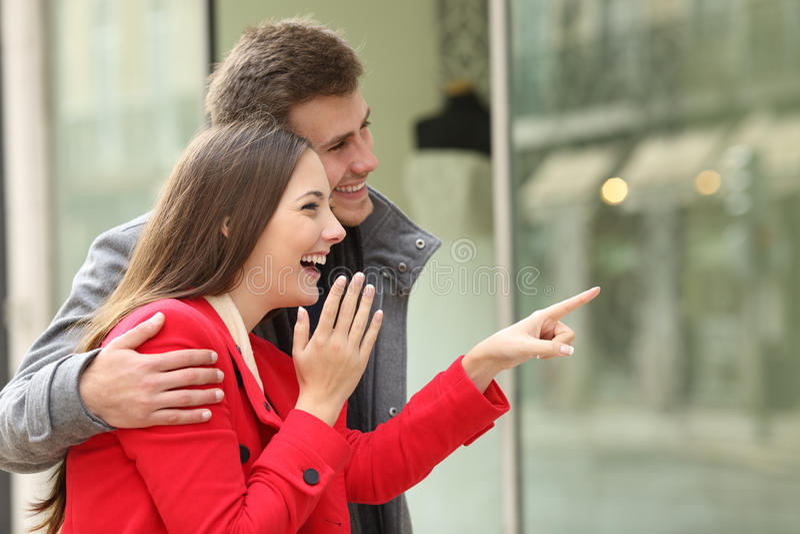 Achats de couples observant dans un devanture de magasin photo libre de droits