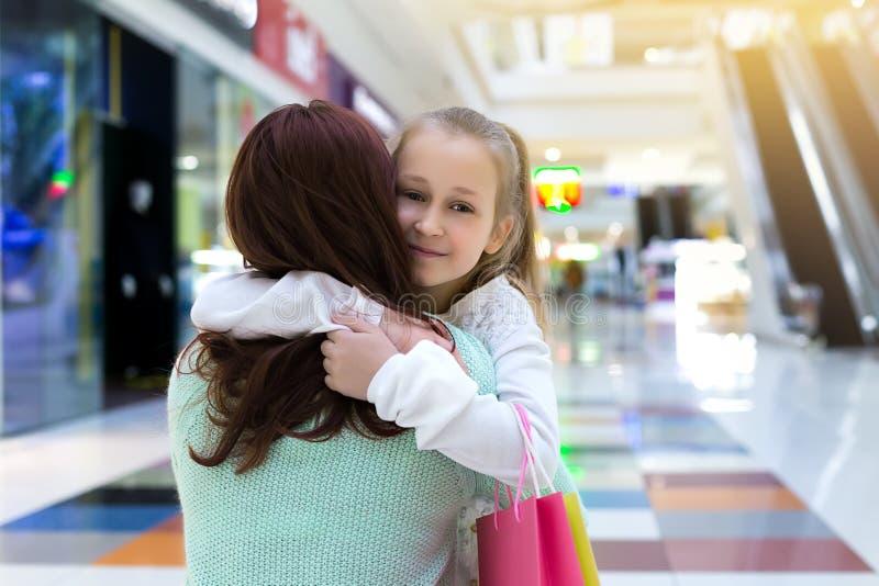 Achats de famille Un enfant étreignant sa mère tenant des sacs à provisions au centre commercial photographie stock libre de droits
