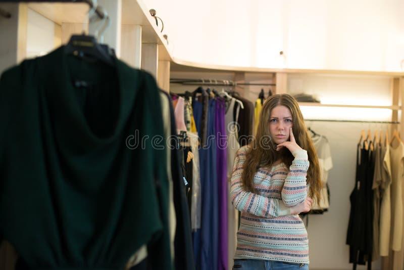 Achats de femme choisissant des robes regardant dans le miroir incertain image stock