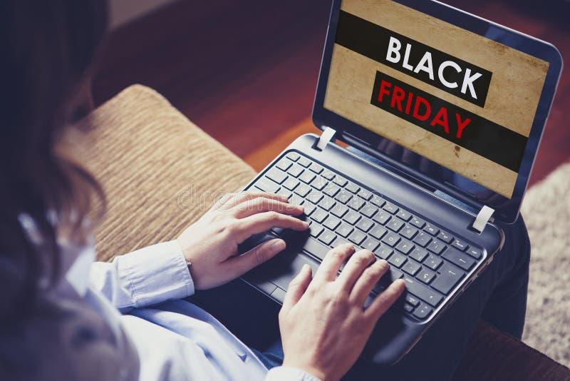Achats de femme par l'Internet au magasin spécial de Black Friday Site Web spécial de Black Friday dans un ordinateur portable photo libre de droits