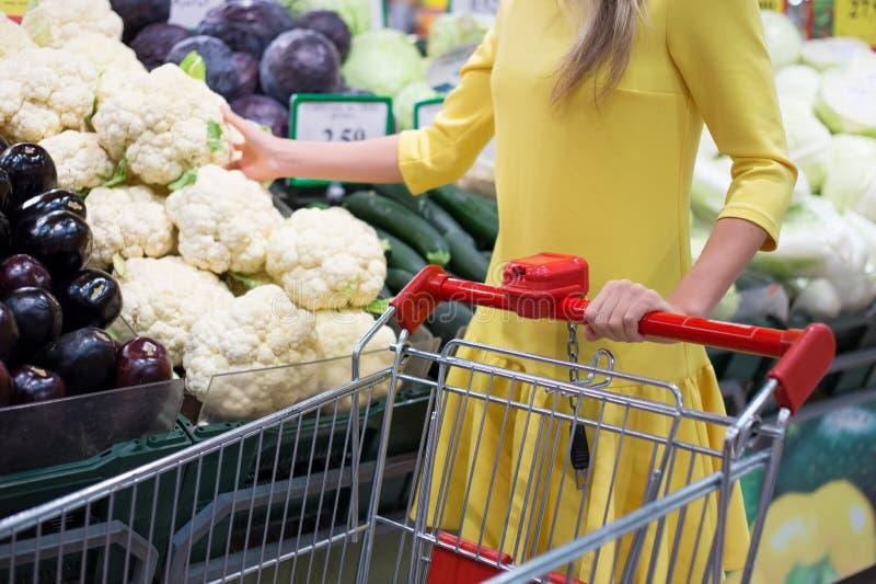 Achats de femme pour des légumes dans le supermarché photo stock