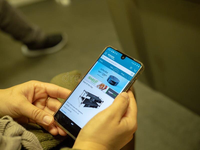 Achats de femme pour Echo Dot sur l'appli mobile d'Amazone sur l'écran d'iPhone tout en permutant sur le métro images libres de droits