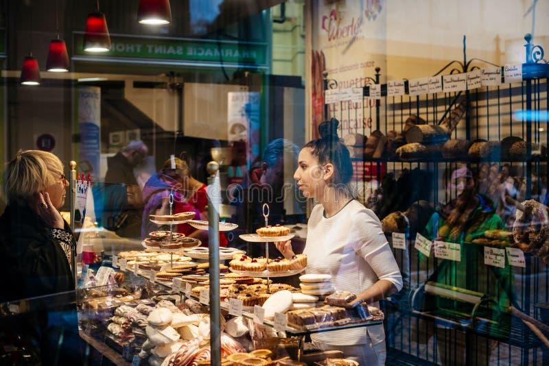 Achats de femme pour la vue de boulangerie de pain de la rue photo stock