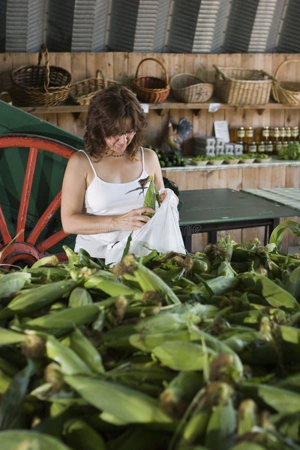Achats de femme pour le maïs photo stock