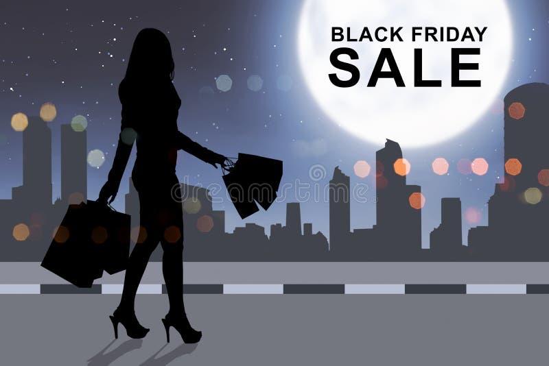 Achats de femme de silhouette avec le sac en papier sur Black Friday photos libres de droits