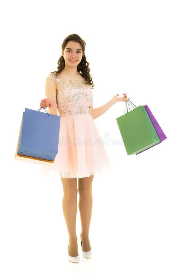 Achats de fille d'adolescent dans un magasin avec de grands sacs en papier images stock