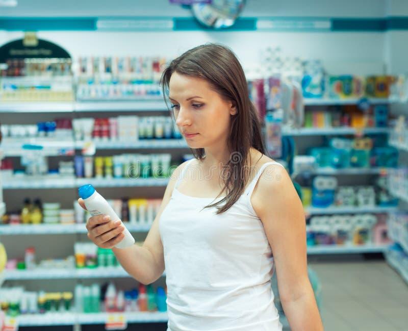 Achats de jeune femme dans les produits domestiques de magasin et le cosmet images libres de droits