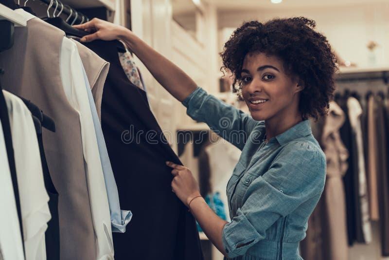 Achats de sourire de jeune femme dans le magasin d'habillement photos stock